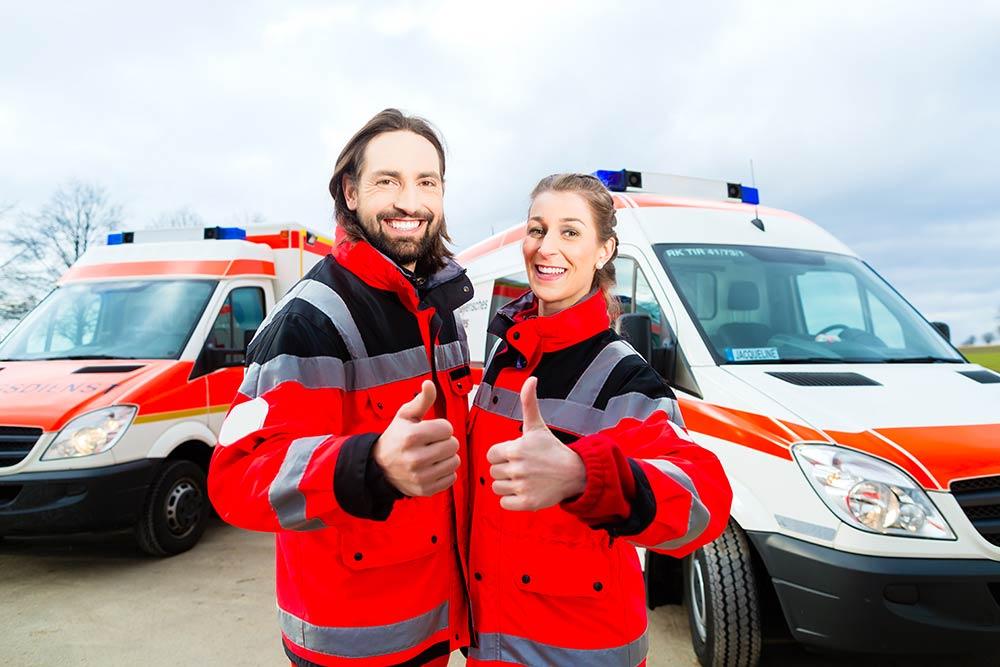 Notfallsanitäter und Rettungsassistentin vor Rettungswagen